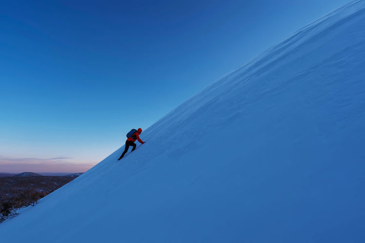 Person skiing on snowcapped mountain against blue sky