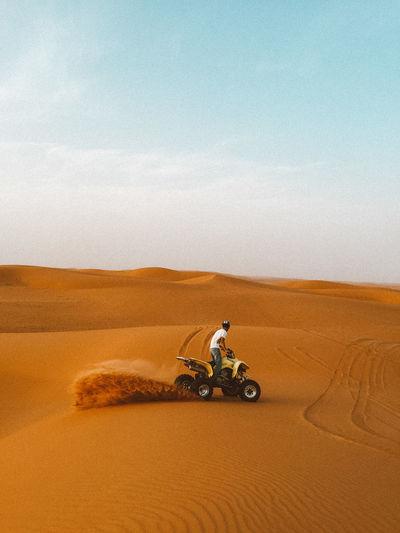 Man riding motorcycle on sand in desert against sky