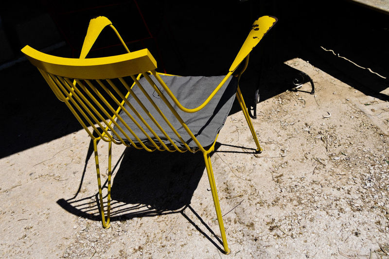 High angle view of chair on field during sunny day