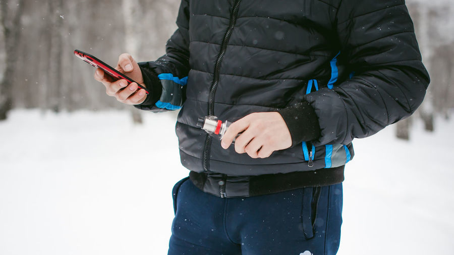 Midsection Of Man Using Mobile Phone While Standing On Snow