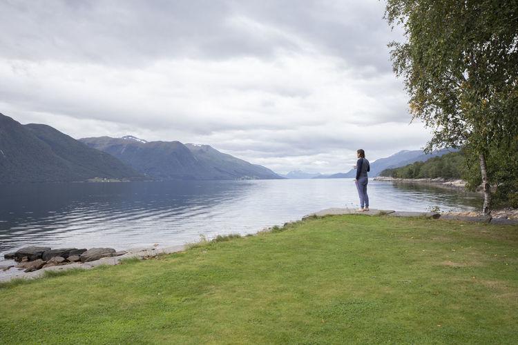 Full length of woman standing on lake against sky