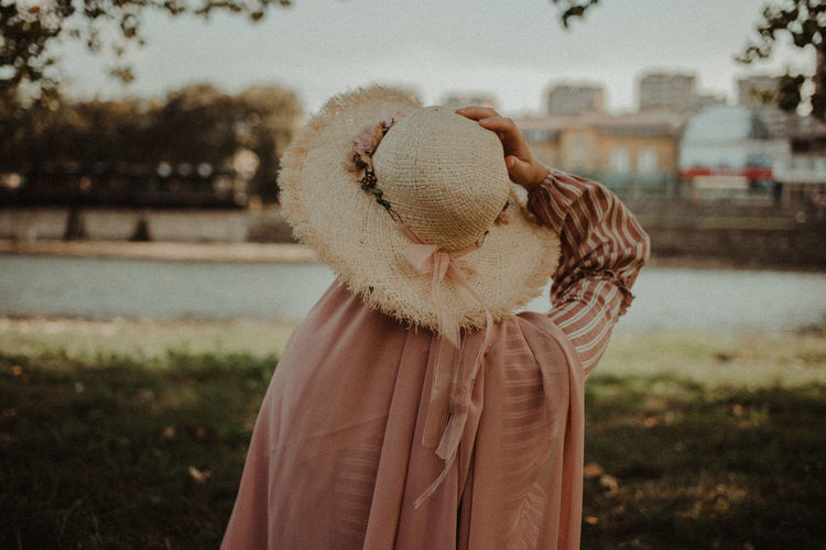 Rear view of woman wearing hat standing on land
