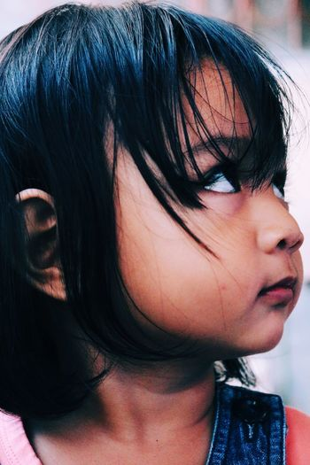 Close-up of thoughtful baby girl with bangs