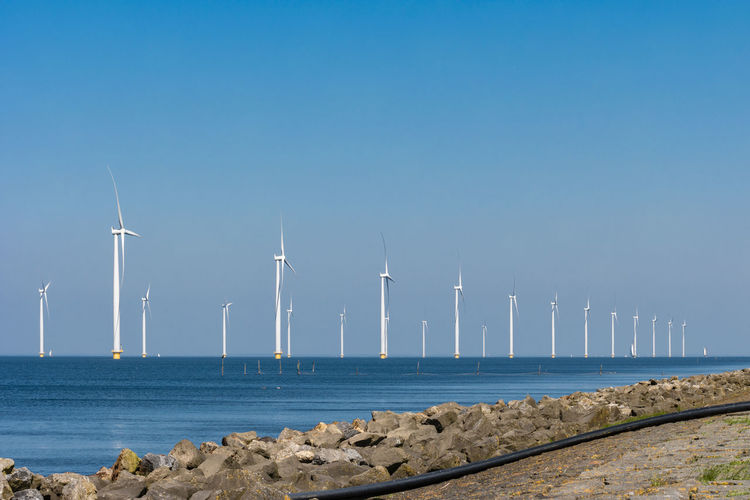 Wind turbines by sea against clear blue sky,