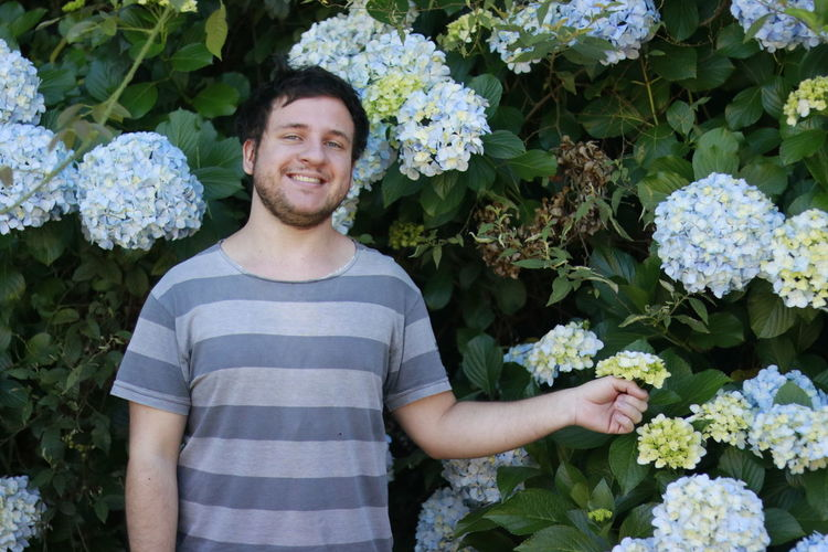 Portrait of smiling man standing by hydrangea flowers at park