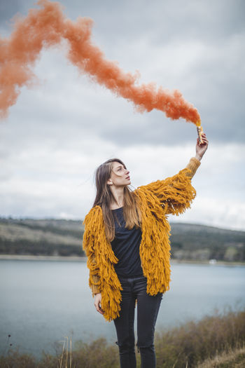 Woman in warm clothing holding distress flare while standing against lake