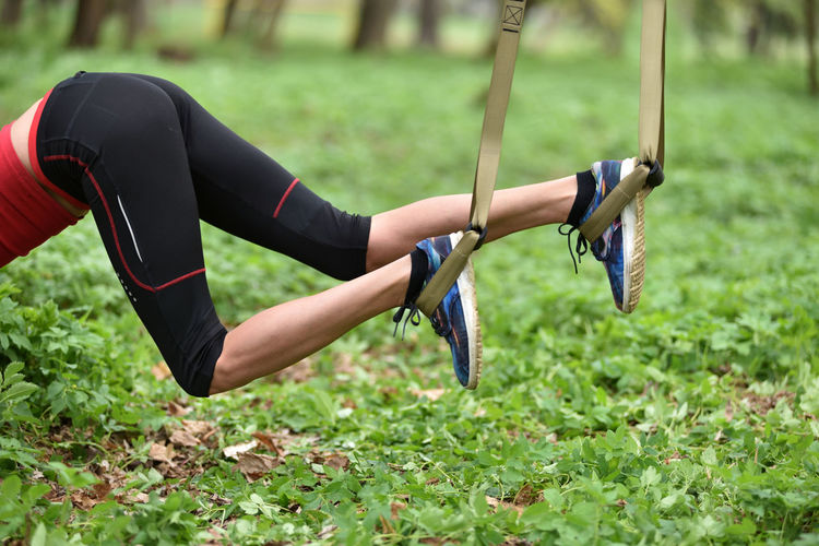 Low section of mid adult woman exercising at public park