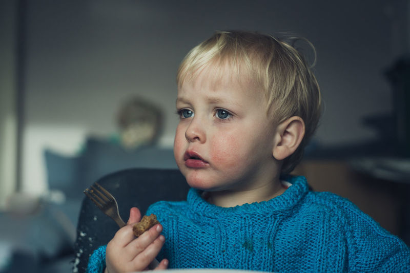 Portrait Of Cute Boy Eating At Home
