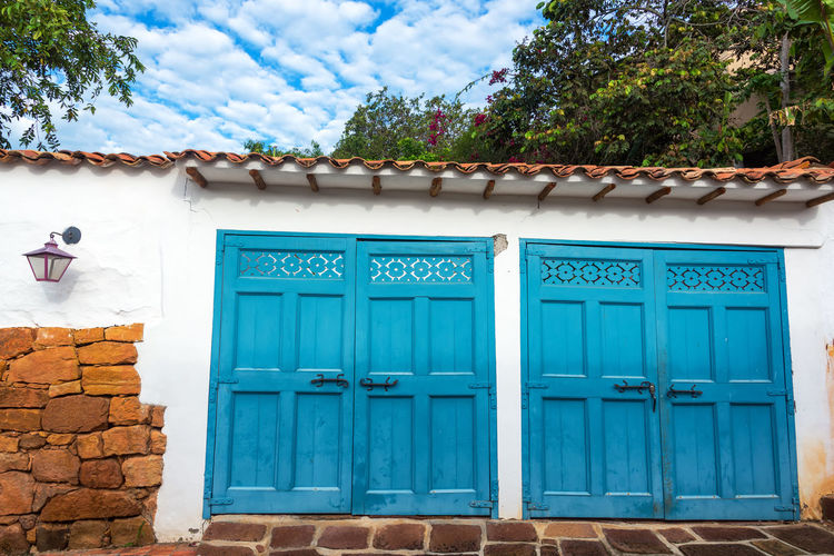 Blue garage doors on a white colonial building in Barichara, Colombia Architecture Barichara Building Colombia Colonial Colorful Exterior Façade Front Historic History House Latin Old Sandstone Santander Southamerica Spanish Street Tourism Town Travel Typical Wall White