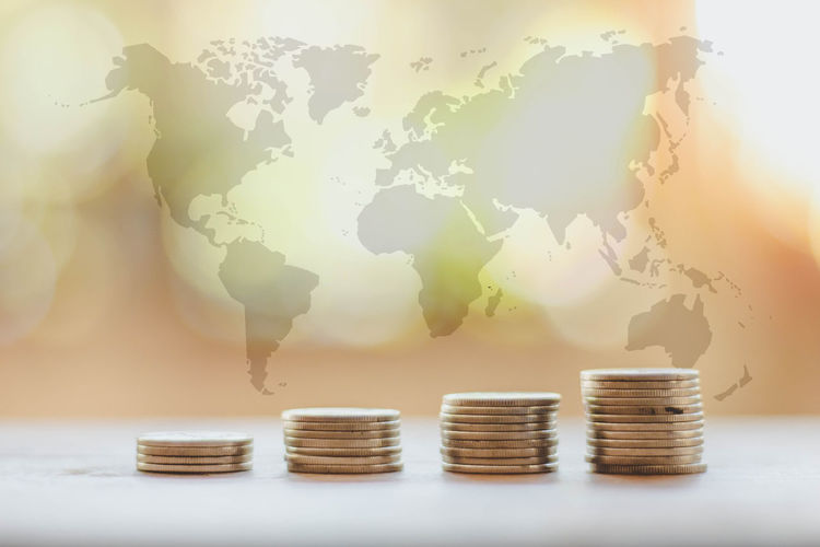 Save money and investment concept with coin stack growing graph with sunlight and world map Economy Growth Light Loan  New Accounting Business Cash Coin Concept Currency Economy Finance Growth Keep It Blurry Money No People Save Stack Wealth World Map