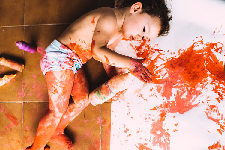 High angle view of child lying with paint on floor at home