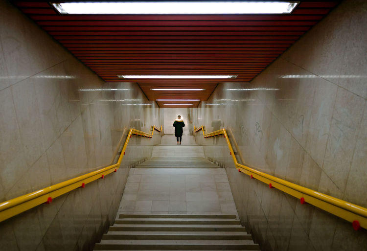 Rear View Of Person Walking Down On Staircase