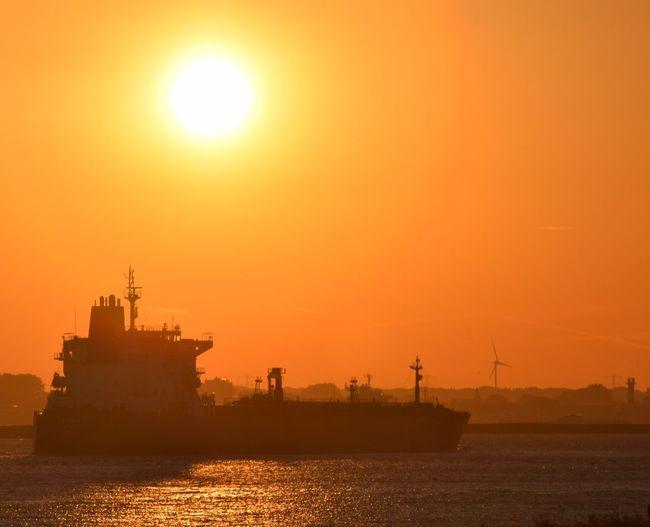 Ship sailing in sea against orange sky