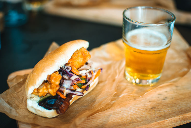 Close-up of a chicken sandwich with a beer glass on table