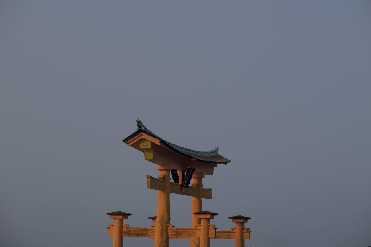 sky, no people, copy space, low angle view, clear sky, birdhouse, built structure, architecture, bird, nature, vertebrate, animal themes, day, animal, wood - material, religion, animal wildlife, building exterior, animals in the wild, outdoors