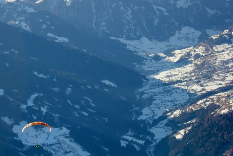 Aerial view of person paragliding against snowcapped mountains