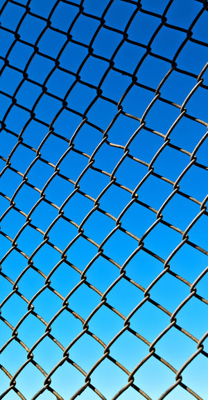 Fence Full Frame Backgrounds Security Protection Safety Chainlink Fence Pattern Barrier No People Boundary Metal Blue Day Low Angle View Sky Grid Close-up Nature Shape Crisscross