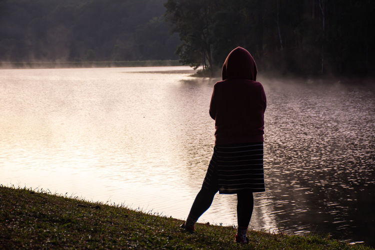 Woman standing on the lawn and mist floating over  water at pang tong reservoir in mae hong son.