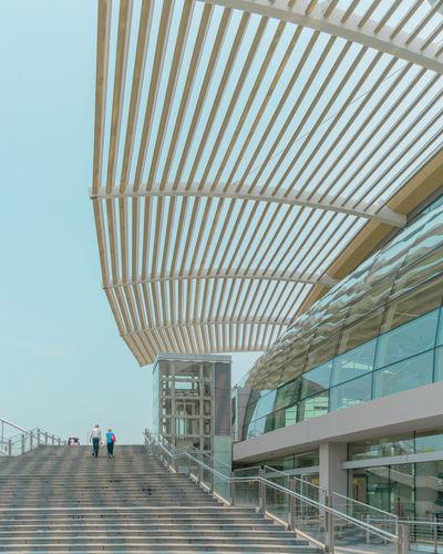 People walking on modern office building against sky