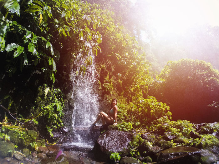 Bali Beauty In Nature Day Leisure Activity Lens Flare Lifestyles Men Motion Nature One Person Outdoors People Real People Rock - Object Sunlight Tree Water Waterfall Young Adult