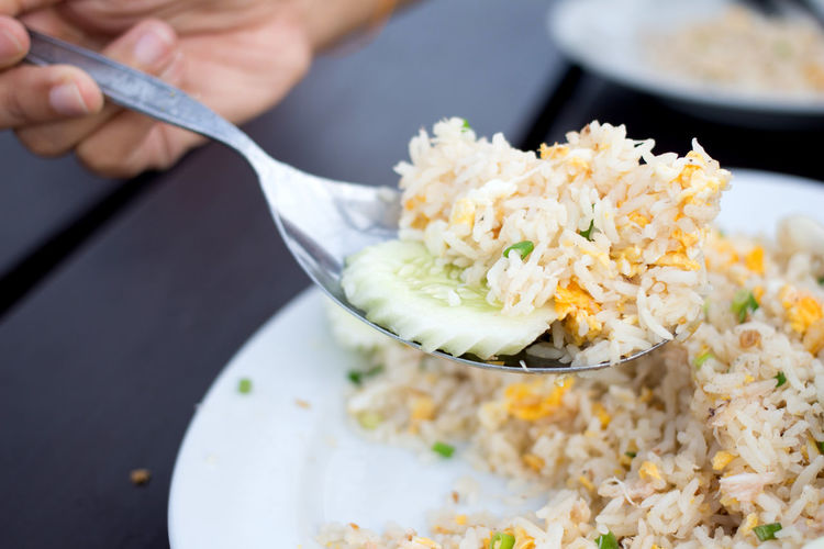 Close-Up Of Hand Holding Fried Rice In Spoon On Plate