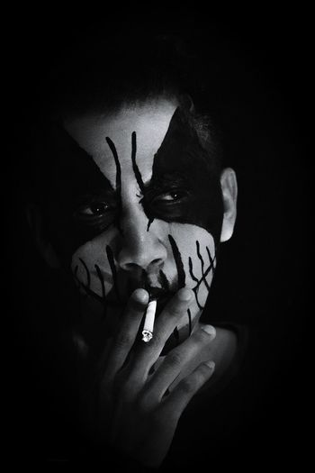Close-up of man with zombie face paint smoking cigarette against black background