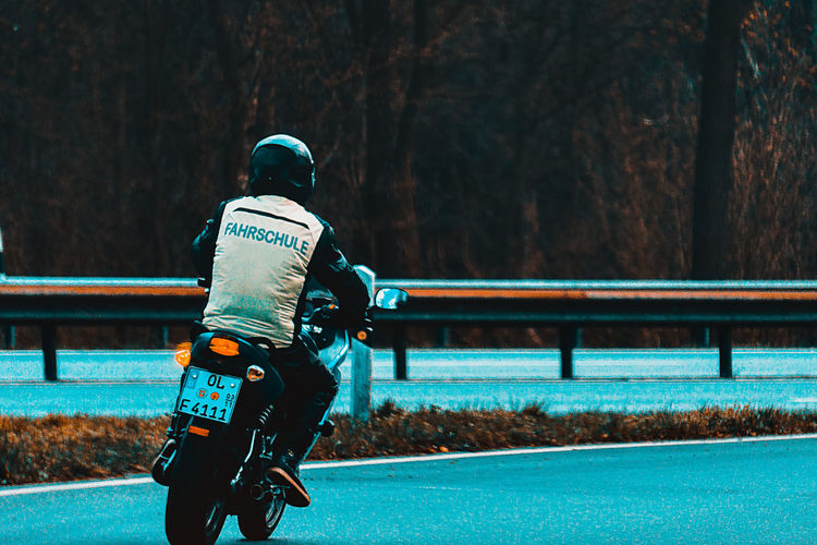 Real People Men Tree One Person Rear View Focus On Foreground Clothing Nature Day Plant Leisure Activity Lifestyles Sport Transportation Railing Outdoors Unrecognizable Person Full Length Three Quarter Length Driving School Motorcycle Motorbike