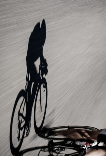 Shadow Of Person Riding Bicycle On Road
