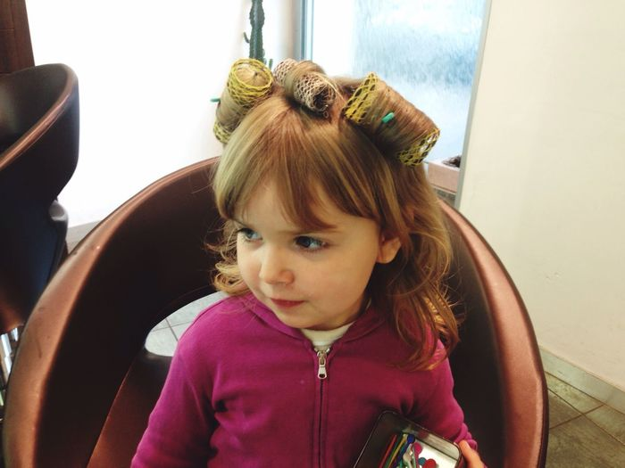High angle view of girl with hair curlers sitting on chair at salon