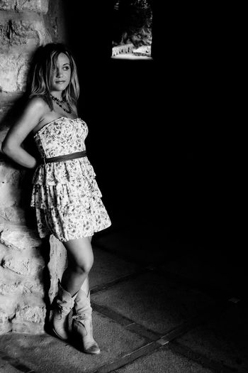 Black and white portrait of young woman leaning against wall at the entrance of a tunnel