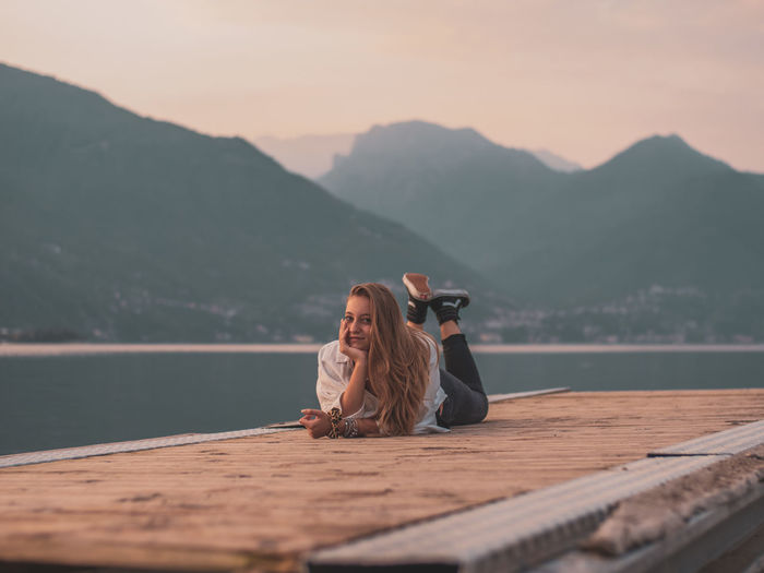 Full length of woman sitting by lake against mountains