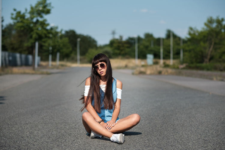 Portrait of beautiful young woman on road