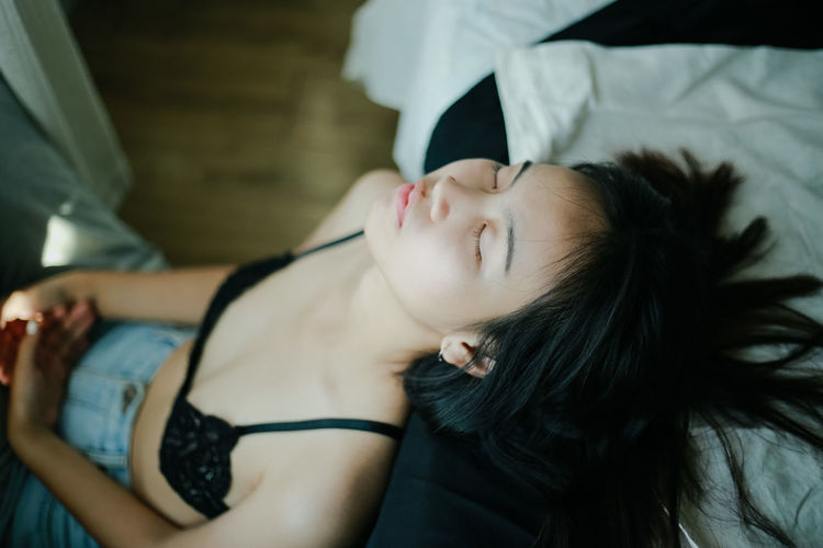Portrait of woman lying down on bed