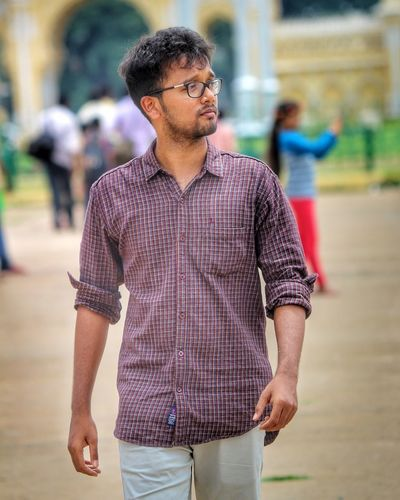 Young man looking away while walking on footpath in city