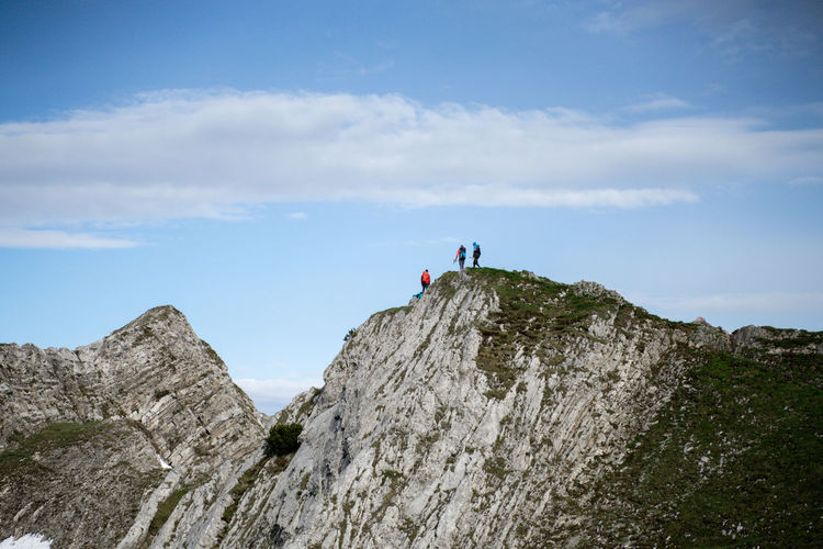 People on rock formations against sky