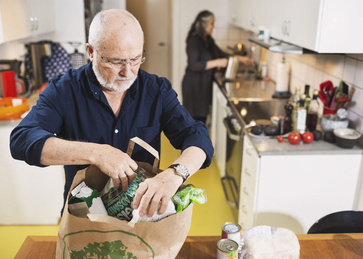 Man holding food on table in kitchen