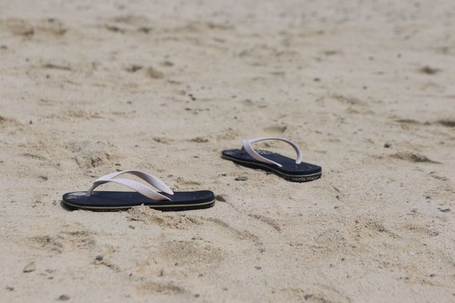 Slippers on the sand Sand Land Beach Shoe Sandal Pair Flip-flop Nature No People Still Life Two Objects Slipper  Day Personal Accessory Outdoors High Angle View Focus On Foreground