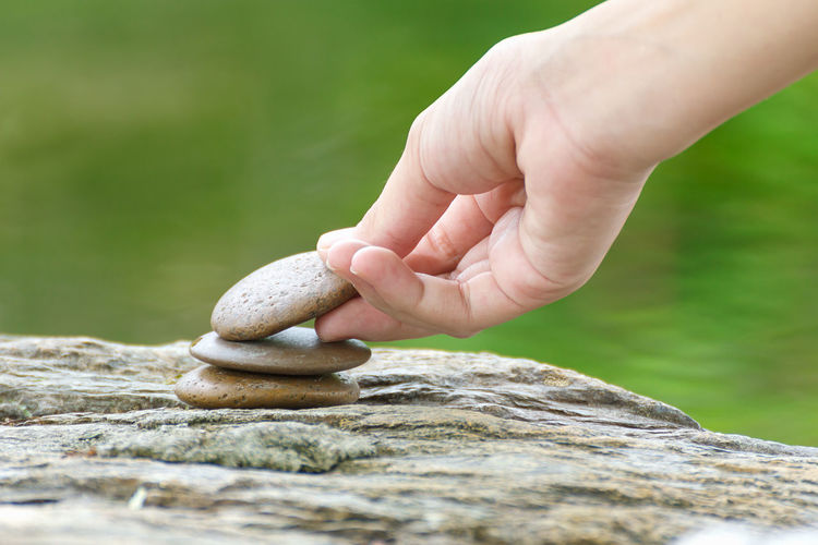 Close-up of hand stacking stones