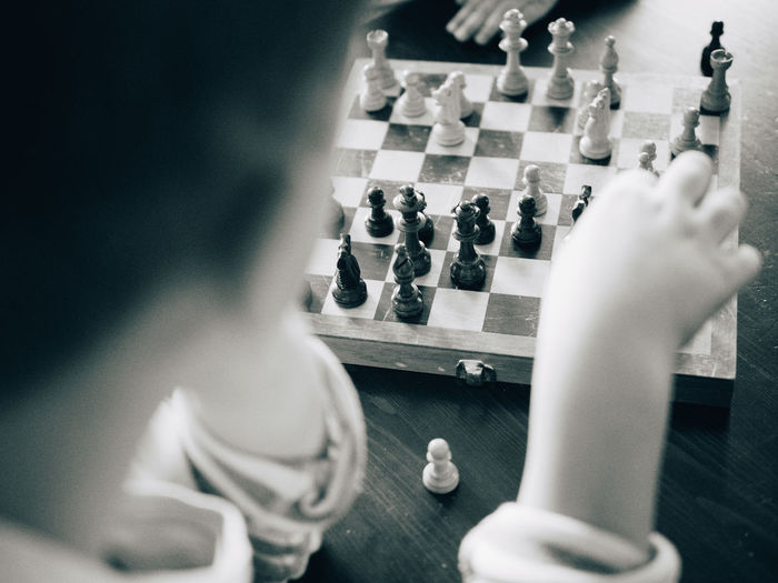 Cropped image of boy playing chess at table