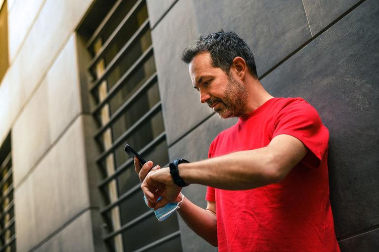 Full length of man standing on mobile phone