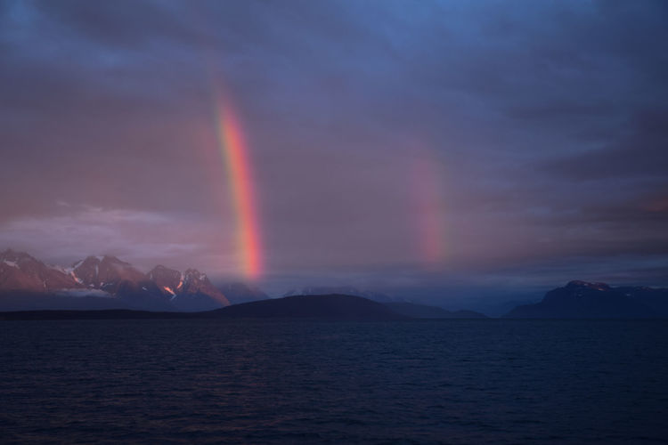Scenic View Of Rainbow Over Mountains Against Sky During Sunset