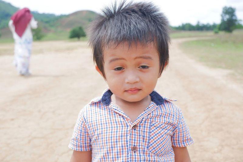 Portrait of cute boy standing on land