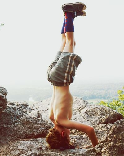 Side view of shirtless boy practicing headstand on cliff during foggy weather