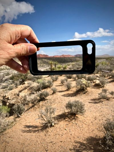 View of desert through phone screen at Red Rock Wash Overlook, Nevada Desert Close-up Day Device Screen Frame Holding Human Body Part Human Hand Mobile Phone Nature One Person Outdoors Photo Messaging Photographing Portable Information Device Real People Sky Smart Phone Technology Tree Wireless Technology Inner Power End Plastic Pollution The Great Outdoors - 2018 EyeEm Awards