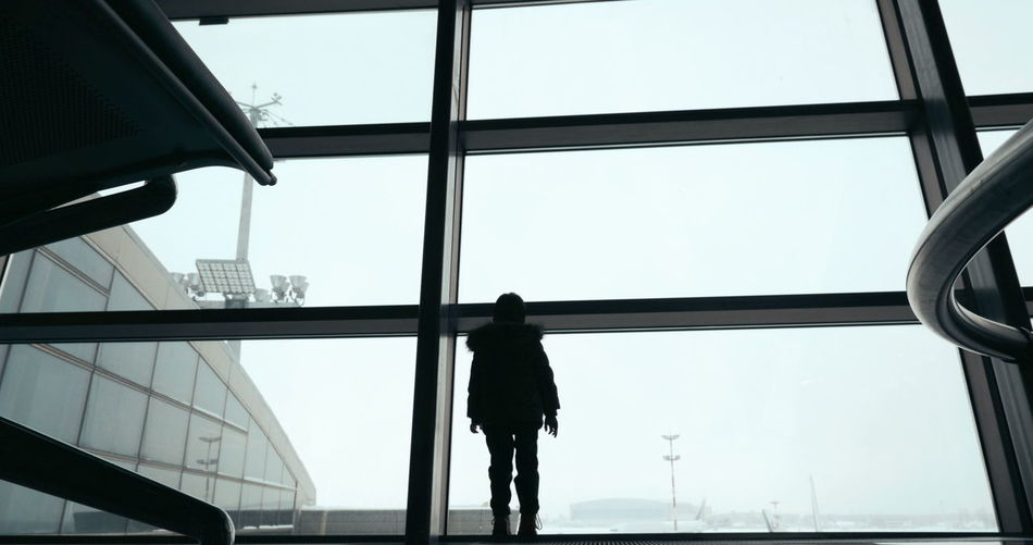 Rear view of silhouette man standing at airport against clear sky