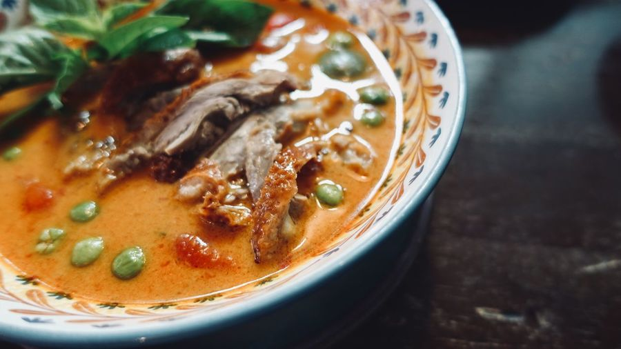 Roasted duck with pineapple,sweet basil leaves and chili peppers in red curry, thai food style.