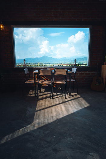 Empty chairs and table against sky