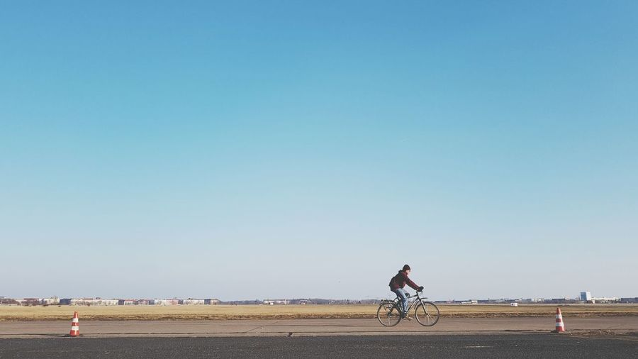 Man riding bicycle against clear sky