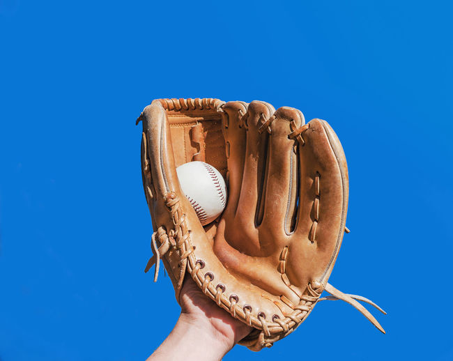 Close-Up Of Human Hand Wearing Glove Holding Ball While Playing Baseball Against Clear Blue Sky