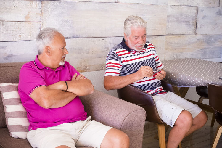 Senior Friends Sitting Against Wall At Home